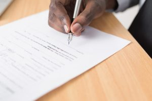 Image of someone holding a pen as they sign a contract