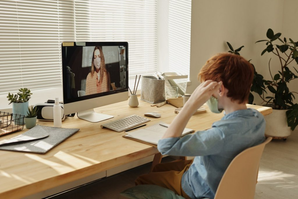 A student at home, wearing a mask, is looking at a teacher on screen