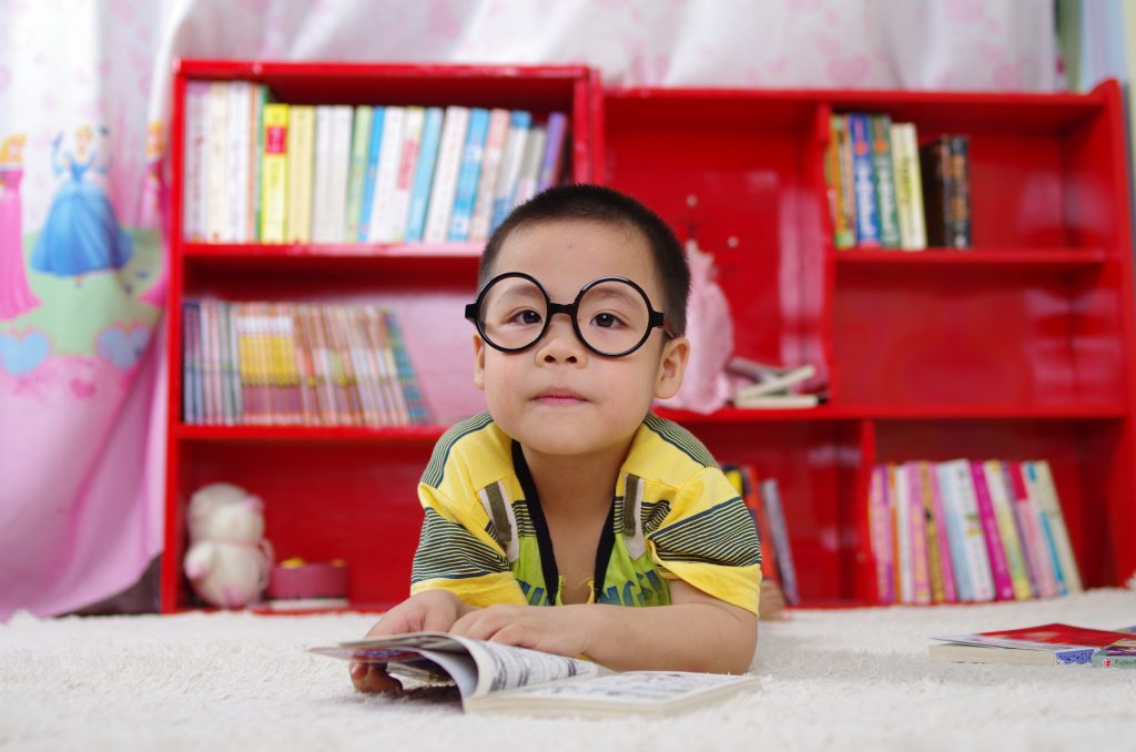 Child reading a book with a bookcase of books behind them