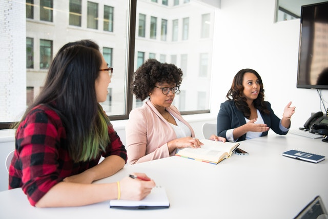 Three women at a workplace table having a discussion