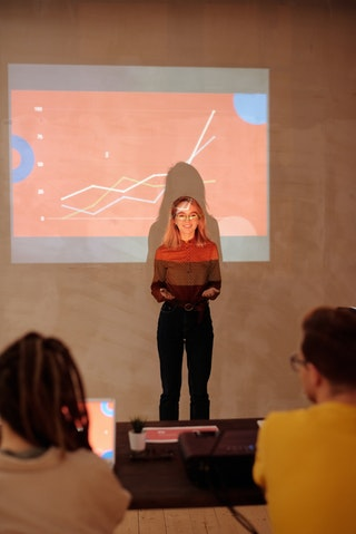 A student stands up to present in front of a projected image
