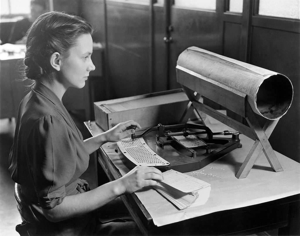 Black-and-white photo of a woman feeding punch cards into a machine